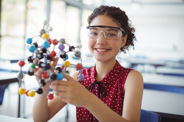 Young girl wearing protective glasses in classroom holding a physical representation of atoms