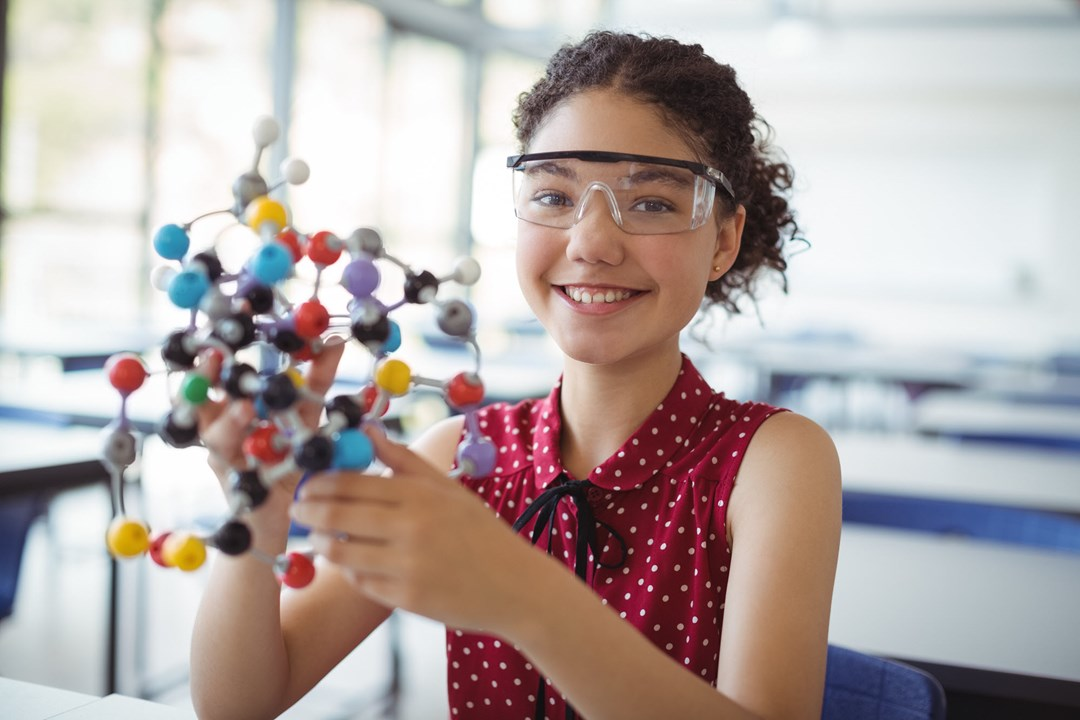 Young girl wearing protective glasses in classroom holding a biology model