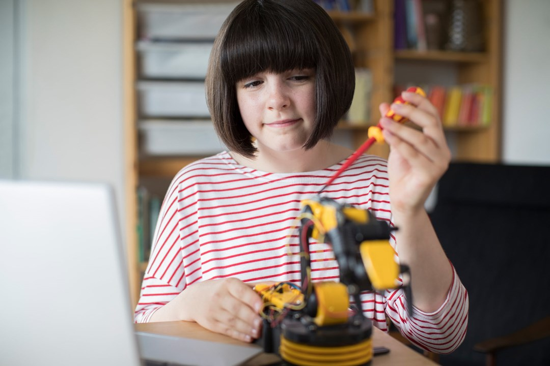 Girl using screwdriver on small robotic device