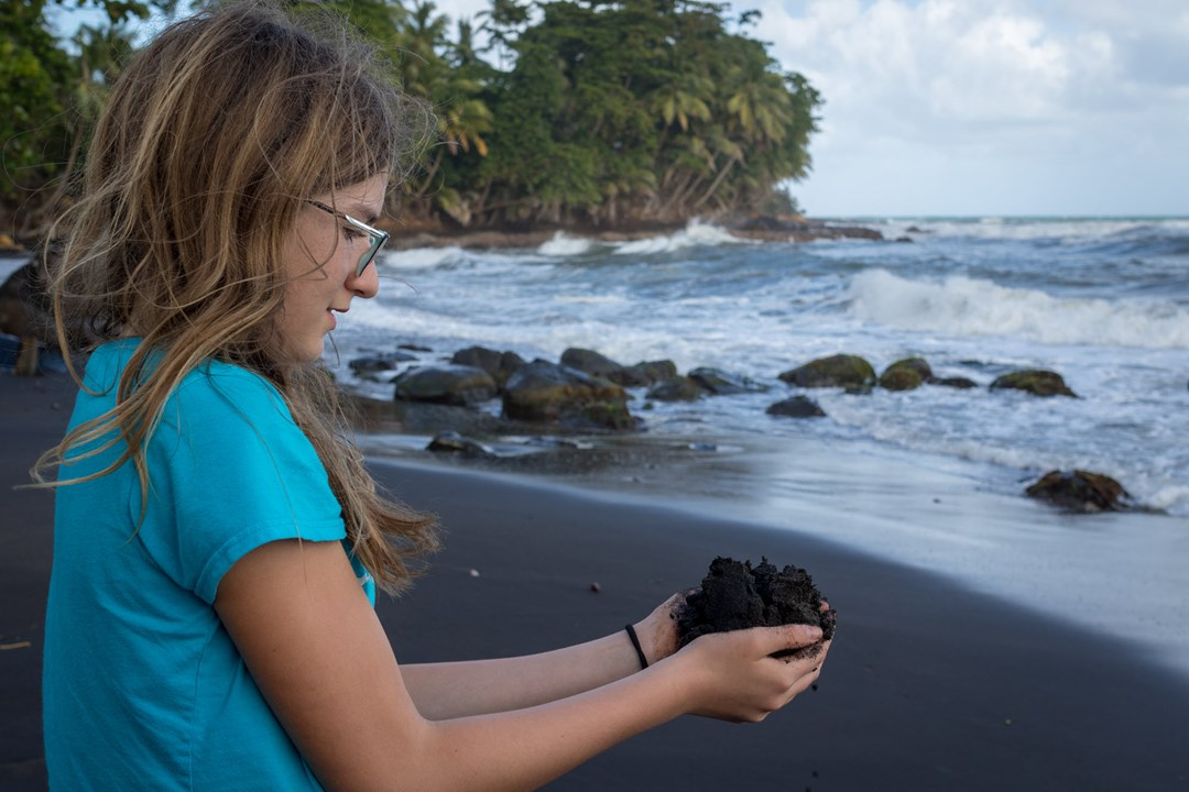 Young girl on the beach holding a handful of soil